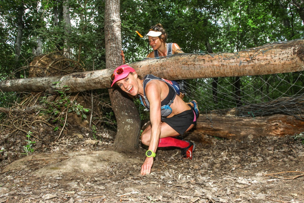 Chantel Neinaber slips under a fallen tree while Katja Sogot waits behind her, on their way to victory in the Women's team race on Stage 3 of the Fairview Dryland Traverse.