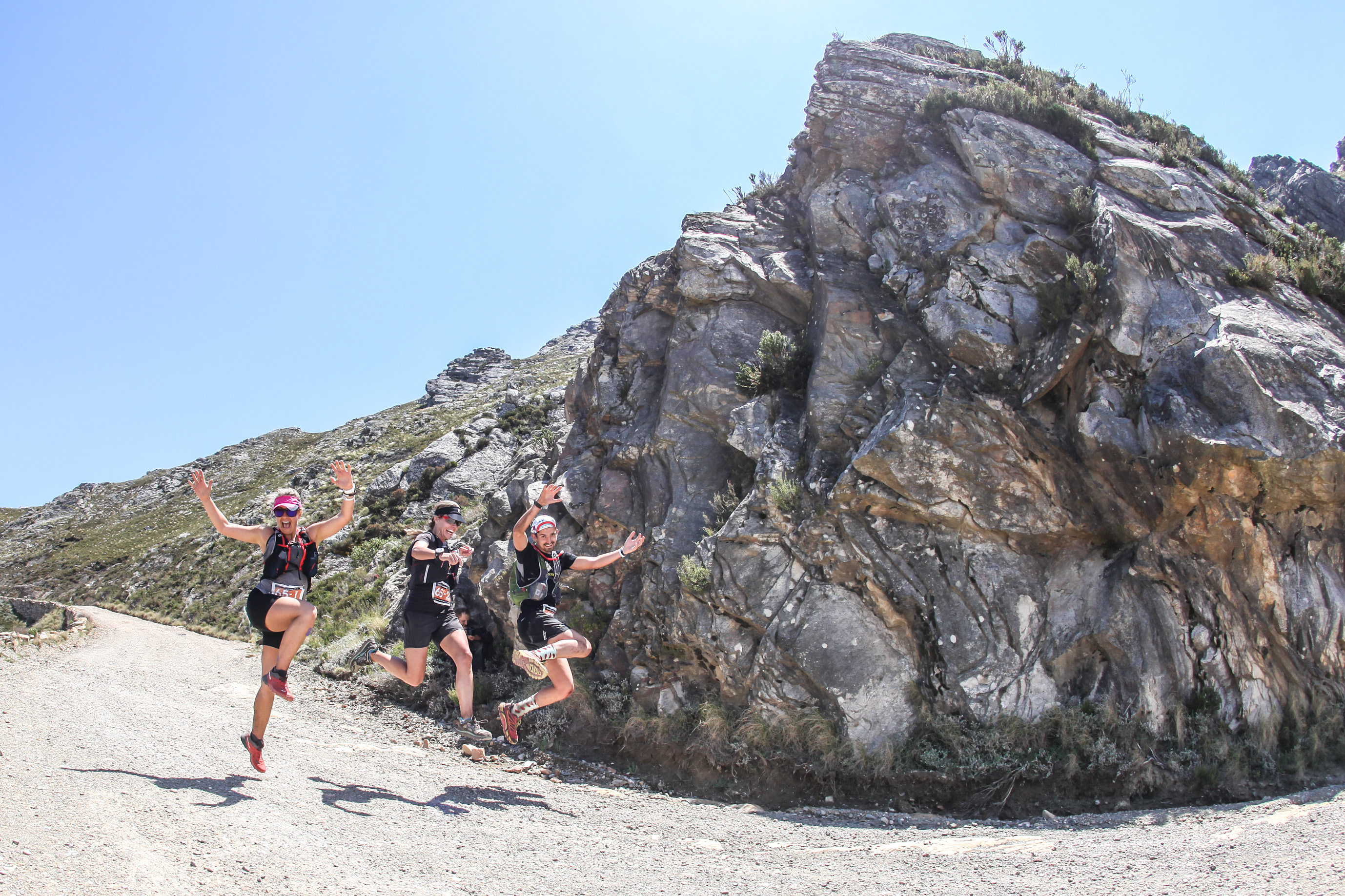 Trail runners jump for joy as they descend the Swartberg Pass towards the stage finish at Kobus se Gat. Photo by Oakpics.com.